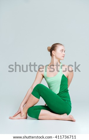 Beautiful woman doing stretching exercise isolated on a white background - stock photo
