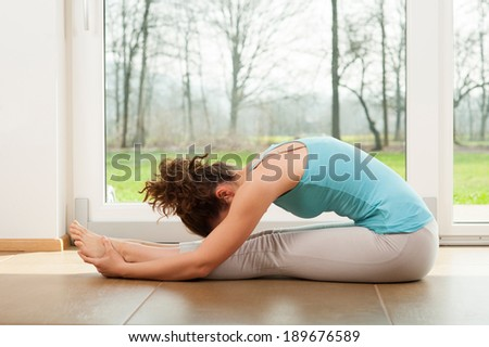 Beautiful woman doing stretching exercises indoor in front of the window - stock photo