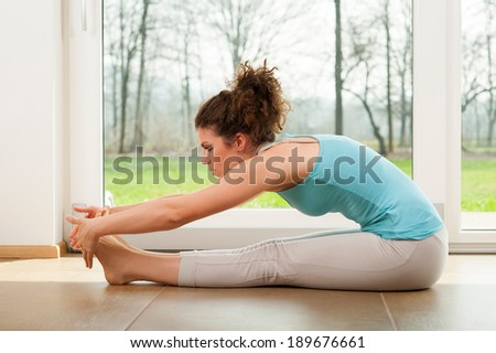 Beautiful woman doing stretching exercises indoor in front of the window