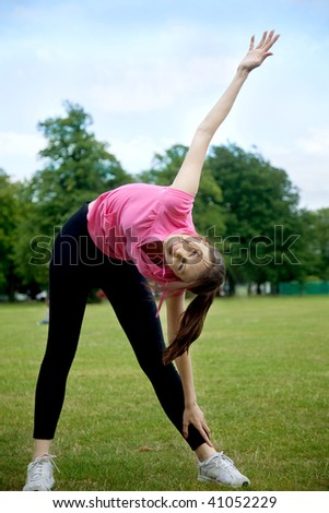 beautiful woman doing stretching exercises outdoors - stock photo