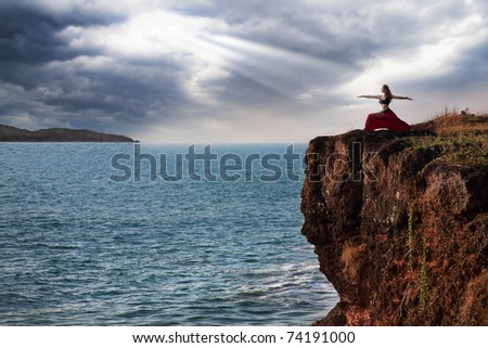 Beautiful woman doing virabhadrasana warrior yoga pose on the cliff near the ocean with dramatic sky at background in India - stock photo