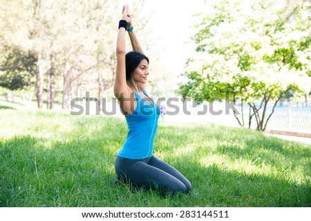 Beautiful woman doing yoga exercises on the green grass in park - stock photo