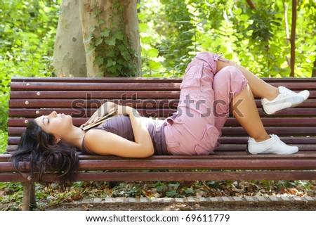 Beautiful woman dreaming after reading in a park bench. - stock photo
