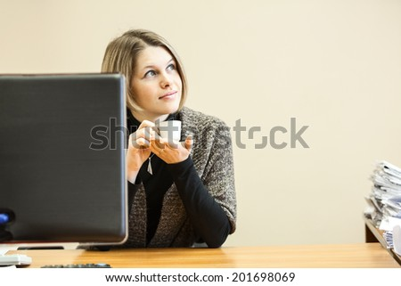 Beautiful woman dreaming with coffee cup at working place - stock photo