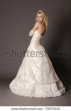 Beautiful woman dressed as a bride over gray background. - stock photo
