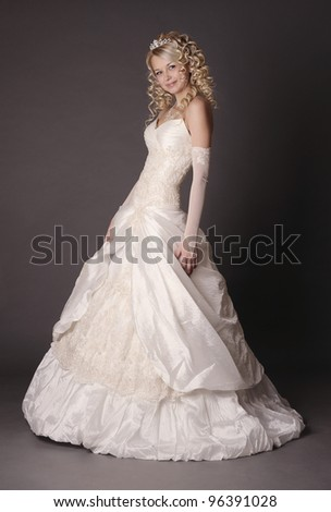 Beautiful woman dressed as a bride over gray background.