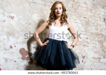 Beautiful woman dressed in black ballet skirt. She stands near the brick wall.