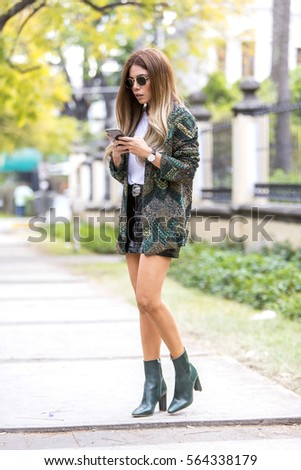 Beautiful woman dressed in fashion texting on her cell phone on the street
