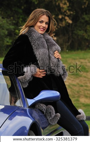 beautiful woman dressed in luxurious fur coat; leaning on a blue sports car - stock photo