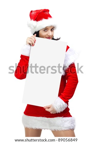 Beautiful woman dressed in santa claus holding a blank board - stock photo
