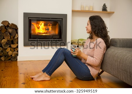 Beautiful woman drinking a hot tea at the warmth of the fireplace - stock photo