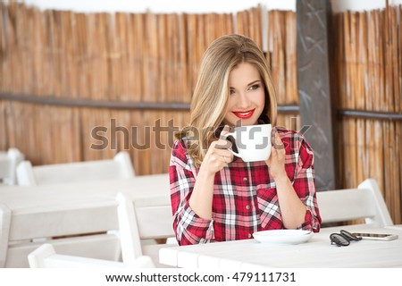 Beautiful woman drinking cappuccino coffee in the summer outdoor cafe.Coffee break. Coffee time