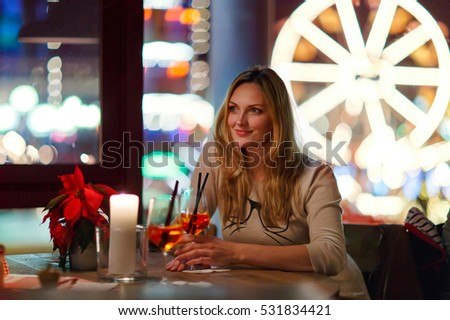 beautiful woman drinking champagne cocktail after work in an indoor cafe and restaurant in London, United Kingdom. Christmas market with ferris wheel and lights on background. Happy girl dreaming