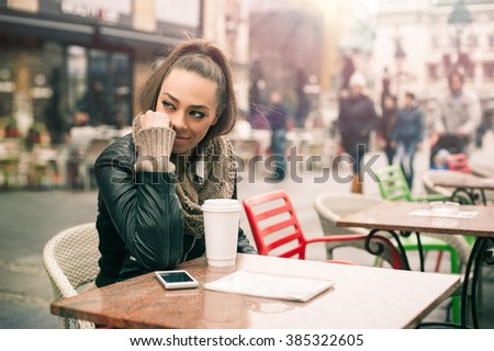 Beautiful woman drinking coffee at the cafe. Pretty young woman drinking coffee with her mobile phone - stock photo