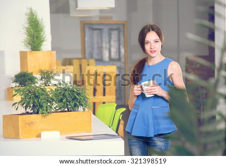 Beautiful woman drinking coffee in the morning at office. Take a break. Come early. Work late. Girl student holding a cup of coffee or tea. - stock photo