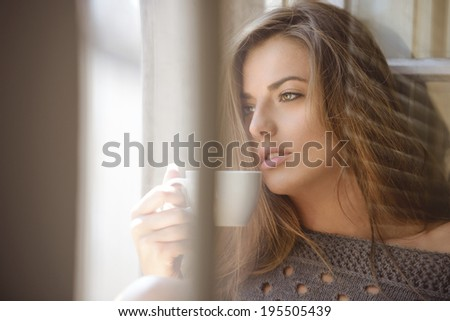 beautiful woman drinking coffee in the morning sitting by the window. - stock photo