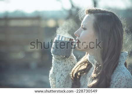 beautiful woman drinking coffee over sunset scenery. focus mouth and cup,  toned filter image - stock photo