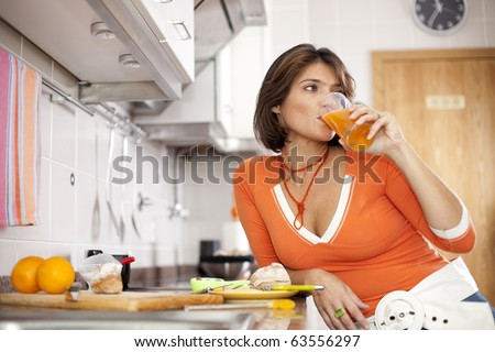 beautiful woman drinking her orange juice and looking natural at her kitchen (selective focus with shallow DOF) - stock photo