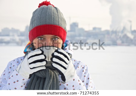 Beautiful woman drinking hot tea on a frozen river on the background of the city. Winter landscape.