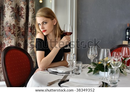 beautiful woman drinking red wine in a luxury restaurant - stock photo