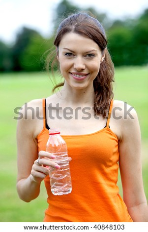 beautiful woman drinking water after finishing her running session - stock photo