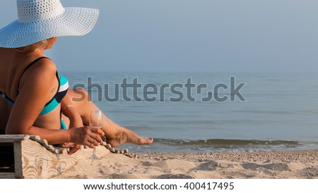 Beautiful woman drinking wine and sunbathing - stock photo