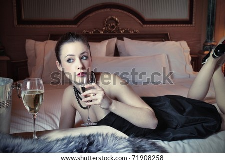 Beautiful woman drinking wine on a bed in a luxury hotel room - stock photo