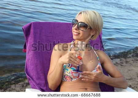 Beautiful woman drinks champagne at the seaside - stock photo