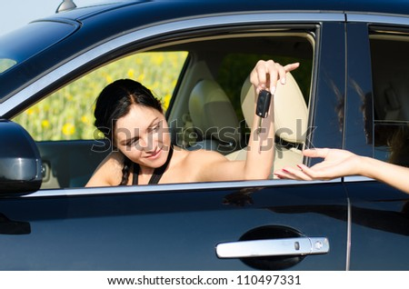 Beautiful woman driver being handed her car keys through the open car window by a female hand