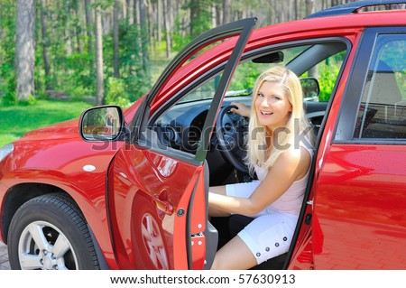 beautiful woman driver in red shiny car opens the door - stock photo
