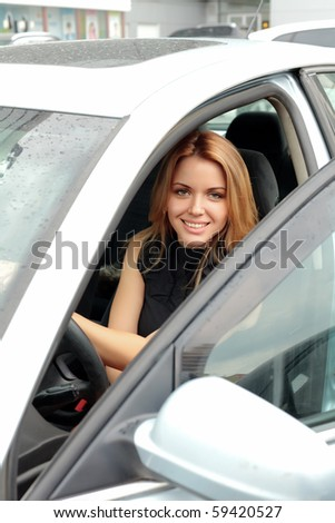 beautiful woman driver in silver shiny car opens the door - stock photo