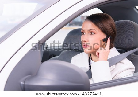 beautiful woman driver is safely talking phone in a car using a headset - stock photo