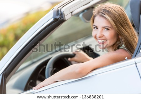 Beautiful woman driving a car and looking very happy - stock photo