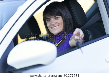 Beautiful woman driving her new white car - stock photo