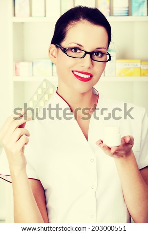 Beautiful woman druggist is holding some tablets.Healthcare concept. - stock photo