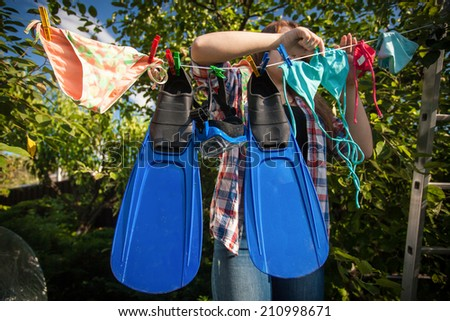 Beautiful woman drying flippers and snorkeling mask on clothesline - stock photo