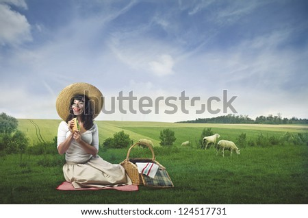 Beautiful woman during a picnic in a beautiful landscape of countryside - stock photo