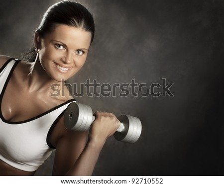 Beautiful woman during fitness with dumbbell. - stock photo