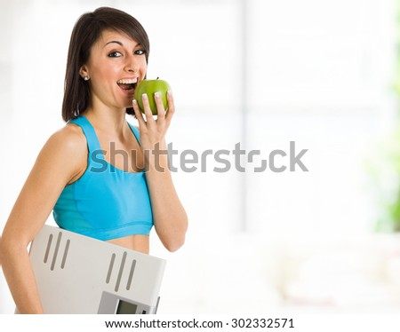 Beautiful woman eating a green apple - stock photo