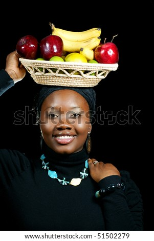 beautiful woman eating an apple and balancing a basket of fruits on her head - stock photo