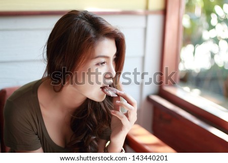 Beautiful woman eating cookies. - stock photo