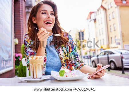 Beautiful woman eating dessert at outdoors cafe