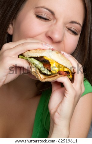 Beautiful woman eating hamburger food - stock photo