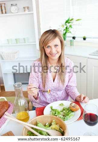 Beautiful woman eating salad in the kitchen at home