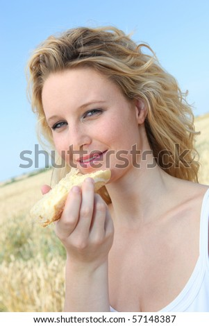 Beautiful woman eating slice of bread with butter