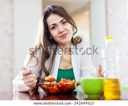 beautiful  woman eating veggie salad with spoon at home - stock photo