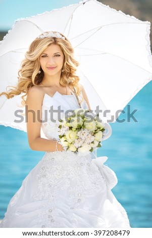 Beautiful woman, Elegant bride with wedding roses bouquet, outdoor portrait. Attractive fiancee with white umbrella, posing over seafront at sunny day. - stock photo