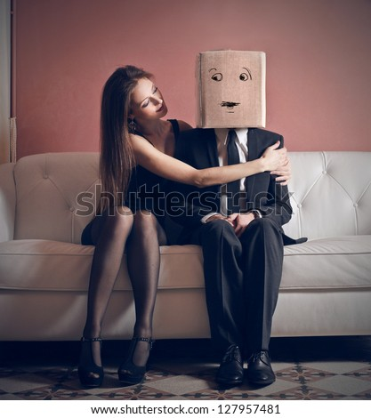 beautiful woman embraces elegant man with box on his head sitting on the couch - stock photo