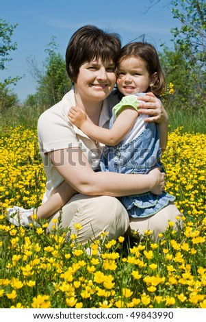 Beautiful woman embracing her happy daughter and sitting among buttercups