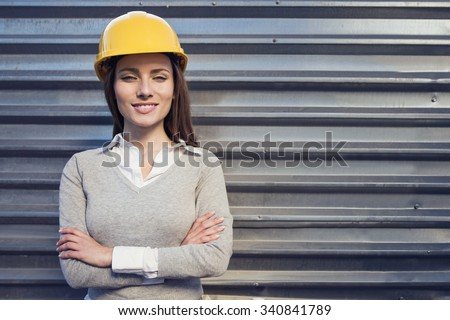beautiful woman engineer is standing in front of an industrial wall - stock photo